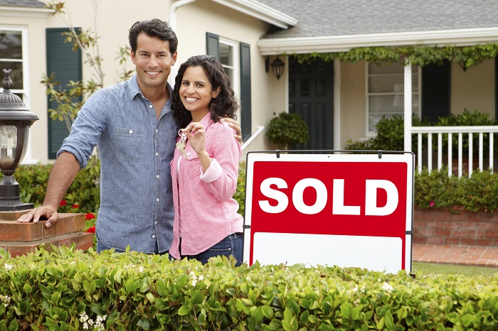 New Homeowners Standing in Front of Home with Keys